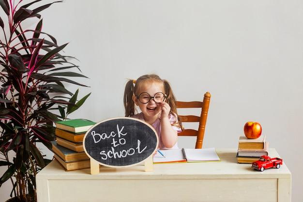 Маленькая милая школьница в очках сидит за партой в школе с учебниками