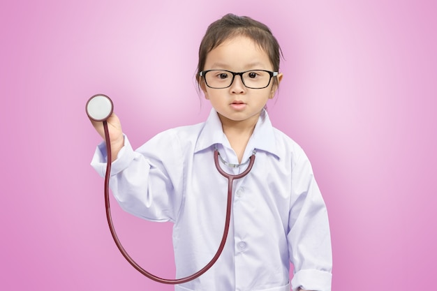 A little cute smiling girl in doctor uniform with stethoscope