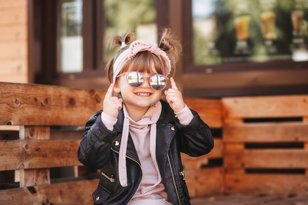 カフェのテラスでサングラスをかけた小さなかわいい笑顔の女の子