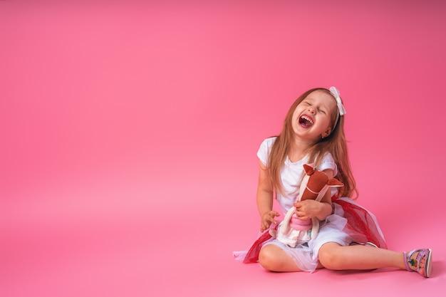 彼女のお気に入りの手作りおもちゃを抱いて彼女の頭に弓を持つかわいい笑顔の女の子
