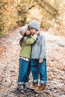 秋の日に一緒に歩いている小さなかわいい笑顔の女の子。友情。幸せな家族の概念