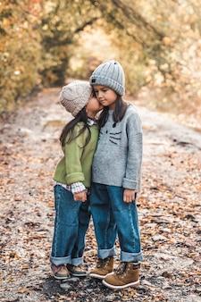 Маленькие милые улыбающиеся девушки вместе гуляют в осенний день. дружба. концепция счастливой семьи