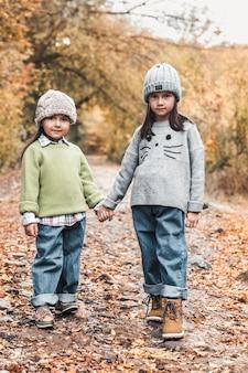 Маленькие милые улыбающиеся девушки гуляют вместе в осенний день