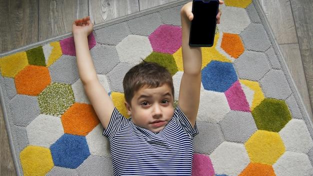 그의 팔을 스트레칭 휴대 전화 또는 스마트 폰을 들고 카펫 손에 누워 작은 귀여운 놀란 아이 소년