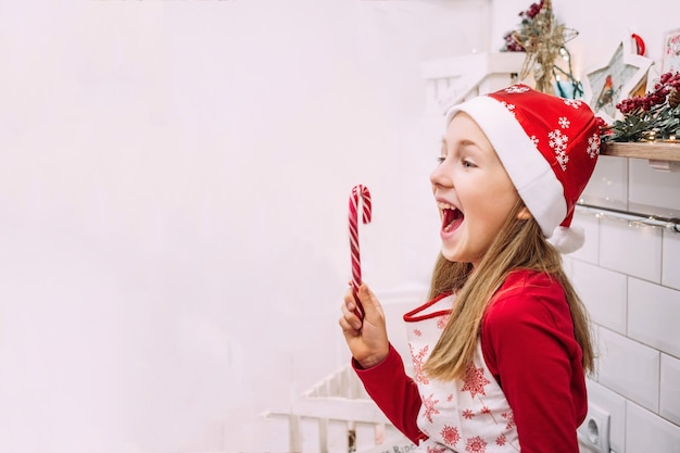 Little cute teenager girl shouts happily in the kitchen with christmas candy in a hat and red sweater.