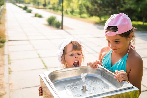 Маленькие милые жаждущие девочки пьют воду из питьевой раковины на улице в солнечный жаркий летний день