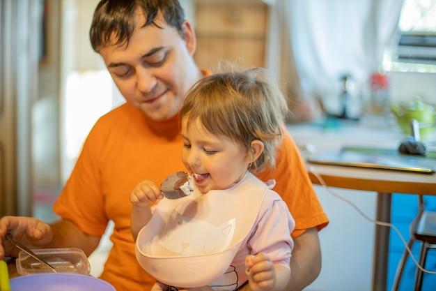 아빠 무릎에 앉아 아이스크림 아이스크림을 먹고 있는 작고 귀여운 소녀, 부드러운 초점.