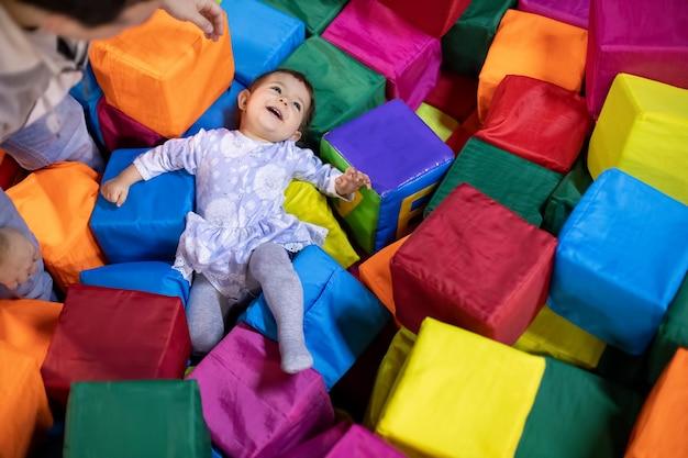 Маленькая милая девочка малыша лежит со счастливым смехом в бассейне с игровой площадкой из кубиков в игровом центре