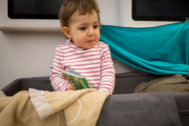 Little cute toddler sit in baby bassinet of an airplane sitting looking around with a startled look