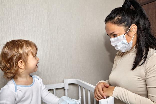 2歳くらいのかわいい白い白人の女の子が医療用マスクで母親を見ています。