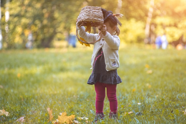 Little cute witch flips a basket and pours autumn leaves in the park
