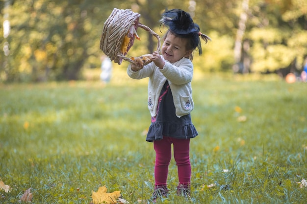 Little cute witch playing with a basket of leaves in the autumn park