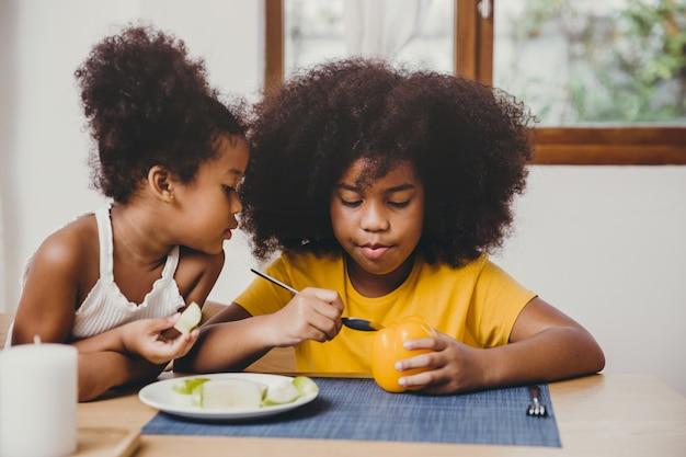 面白そうに見えるかわいい妹がお姉さんが野菜を食べることを学ぼうとしています。