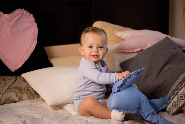 Лежать маленького мальчика милашки сидя в кровати перед сном. детство счастья.