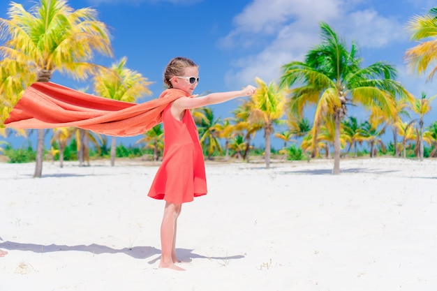 Little cutie girl playing superhero at a tropical beach