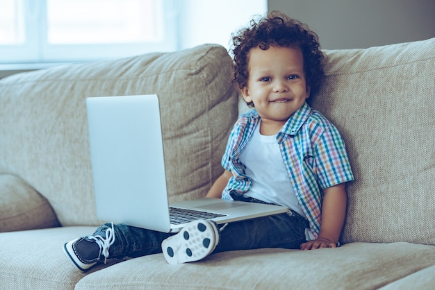 Little cutie with laptop. little african baby boy looking at camera with smile while sitting on the couch at home with laptop on his knees