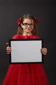 黒の背景のスタジオでポーズをとって赤の小さな黒い髪の少女