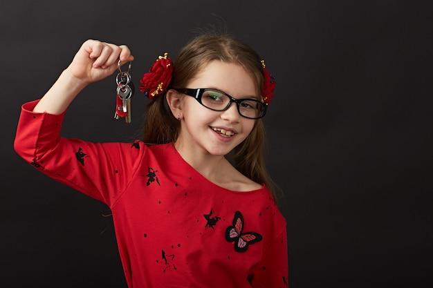 Little dark hair girl in red posing in studio on black background