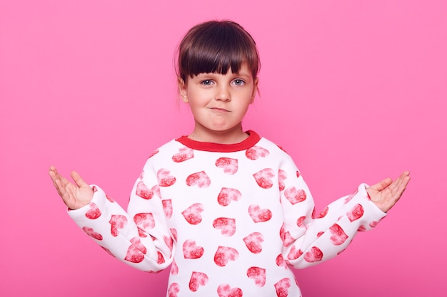 Little dark haired female kid posing with spreading hands aside, looking at camera with frowning face, wearing casual attire, isolated over pink wall.