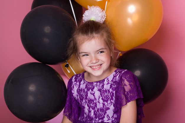 Little dark haired girl with colourful balloons