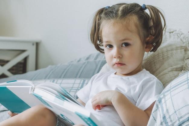 Маленькая темноволосая девочка 24 с двумя хвостиками сидит на кровати с подушками и читает книгу