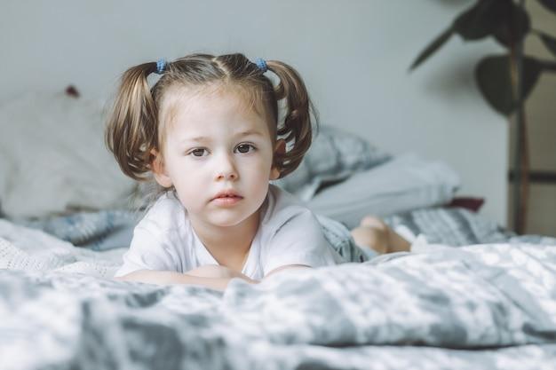 Маленькая темноволосая девочка с двумя хвостиками лежит на кровати на животе и смотрит в кадр