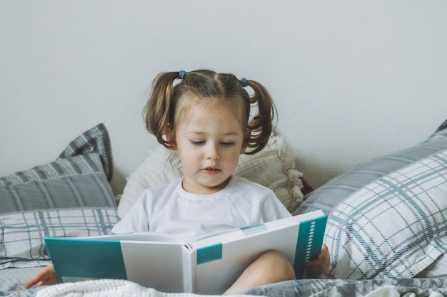 Little darkhaired girl  with two ponytails sits on bed with pillows and reads book
