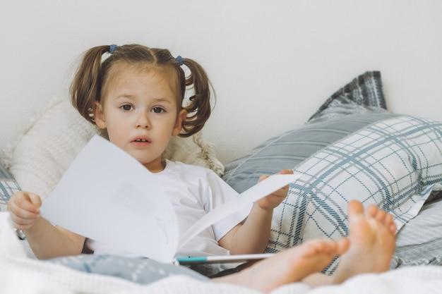 Маленькая темноволосая девочка с двумя хвостиками сидит на кровати с подушками и читает книгу Premium Фотографии
