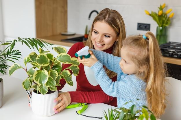 Маленькая дочь и мать опрыскивают и чистят комнатные растения. малыш помогает маме ухаживать за растениями