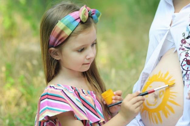 어린 딸이 임신 한 어머니의 뱃속에 태양을 그립니다.