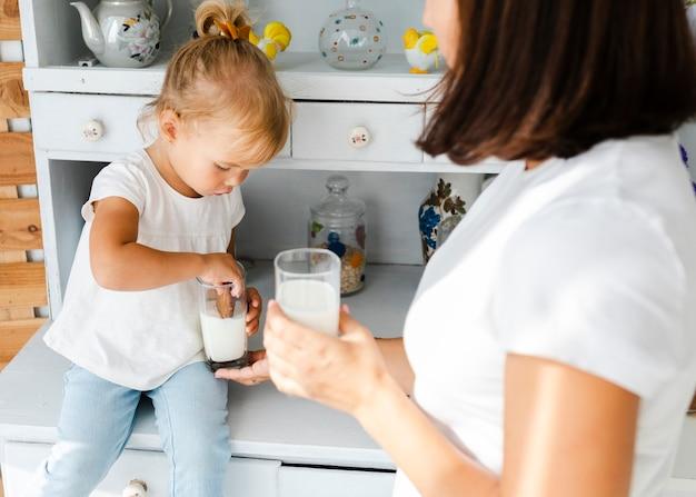 Маленькая дочь ест печенье с молоком