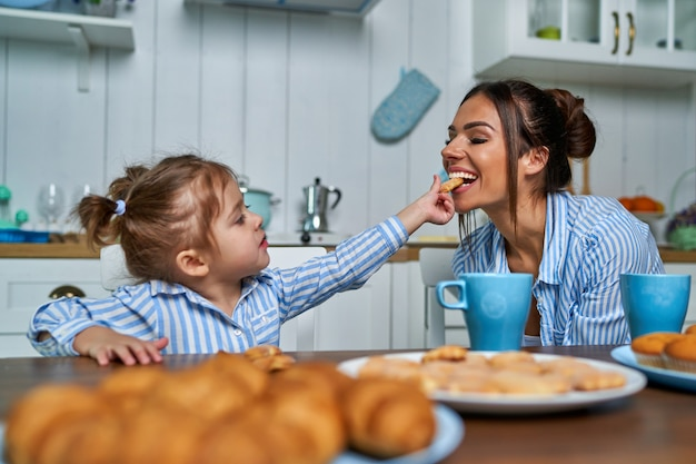 Little daughter feeds her mother with sweet cookies