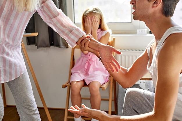 어린 딸 소녀는 그녀의 눈을 감고, 그녀는 집에서 부모 싸움, 깨진 가족, 이혼 개념을 두려워합니다.