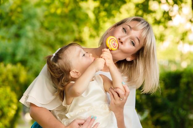 小さな娘は公園で夏に屋外でお母さんに甘いロリポップを与えます