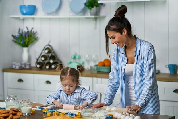 休暇中に母親がケーキを作るのを手伝う小さな娘