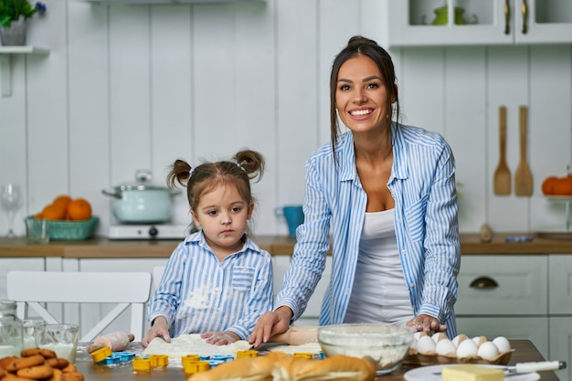 Little daughter helping her mother cooking a cake during the holidays