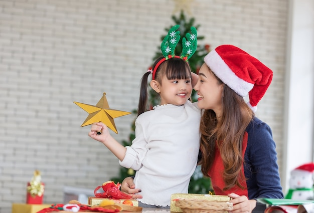 Little daughter holding gold star for decoration christmas tree
