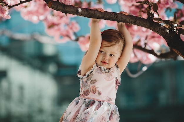 Little daughter holds a branch of blooming pink tree
