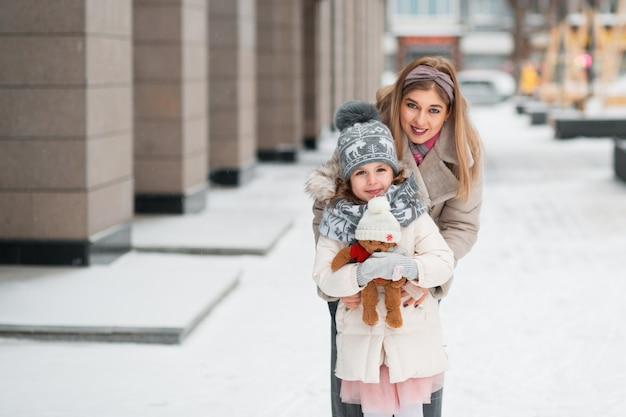 Little daughter hugging with mother and holding teddy bear in winter city