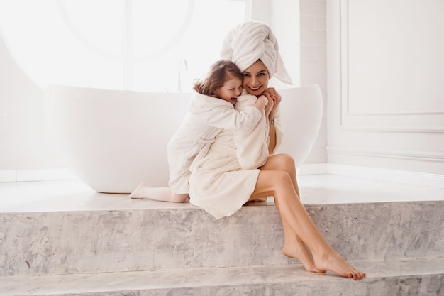 어린 딸이 엄마를 안아줍니다. 밝은 욕실에서 흰색 코트를 입은 엄마와 딸. 위생, 아름다움, 행복한 가족 개념