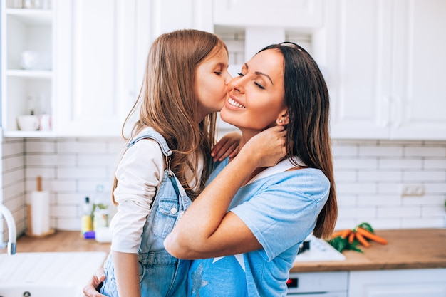 Little daughter kissing and hugging her mother