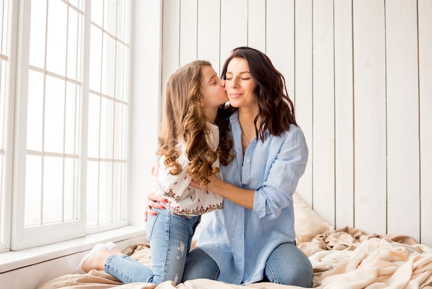 Маленькая дочь целует мать в щеку на кровати