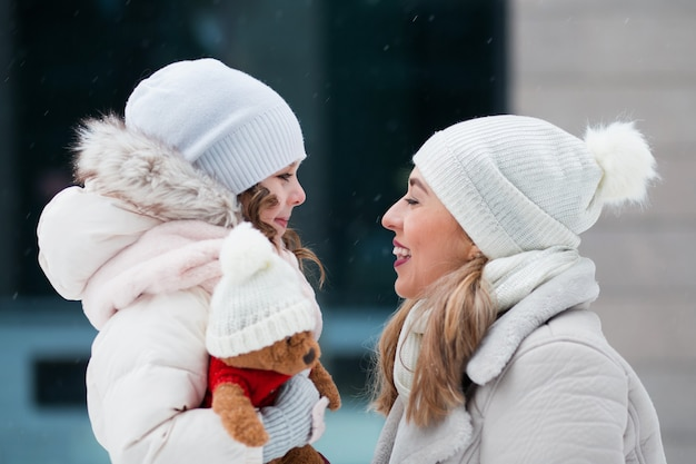 Little daughter looking at mother and holding teddy bear in winter city
