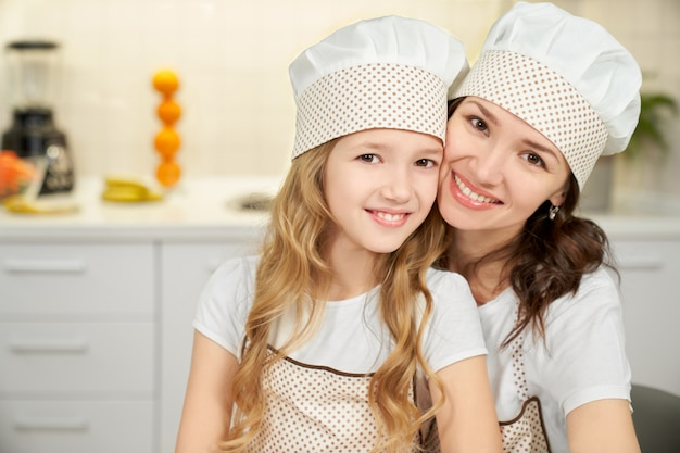 Little daughter and mother in aprons looking at camera.