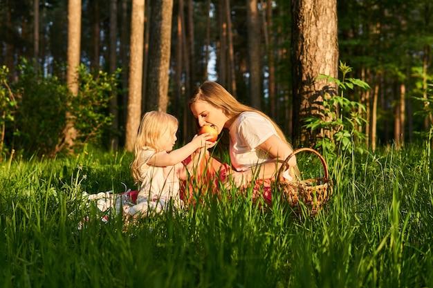 Маленькая дочь делится яблоком с мамой во время пикника в парке