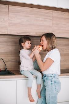 작은 딸이 부엌 표면에 앉아 그녀의 어머니가 사과를 시도하도록주는