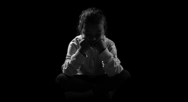 Little daughter sitting while holding her legs in sad emotion. depression and sad concept against black background