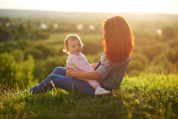 Little daughter smiling, sitting on mother's knees while sunset.