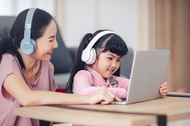 母親と一緒に勉強している小さな娘は、ラップトップでオンラインレッスンを見ます。