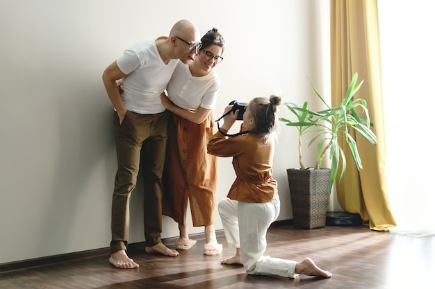 Маленькая дочь фотографирует своих родителей. которые позируют перед камерой.